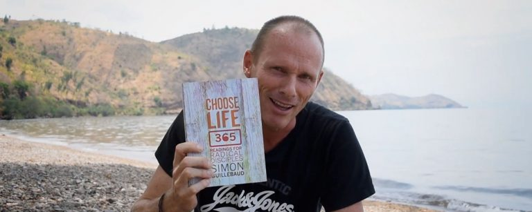 simon holds up the choose life book by a lake