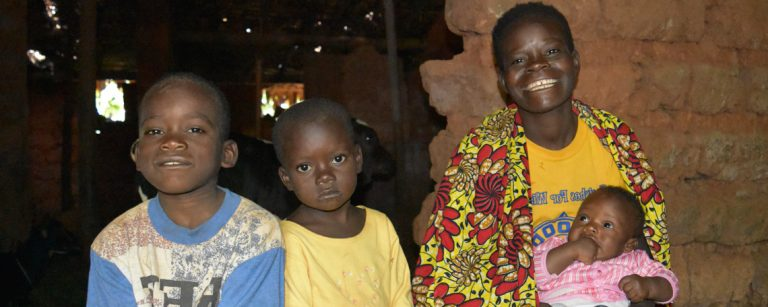 specoise smiles with her three young children in their home
